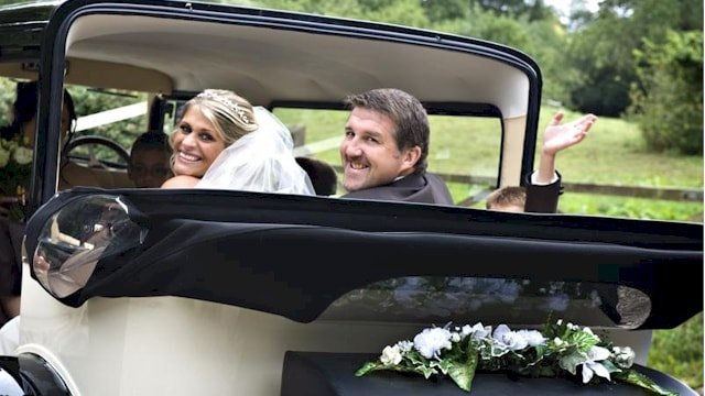 Bride and Groom driving away in the Bramwith Limousine